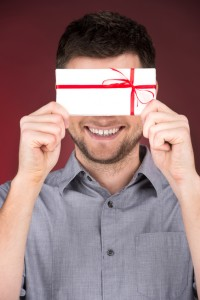 Present gift in hands of smiling man.